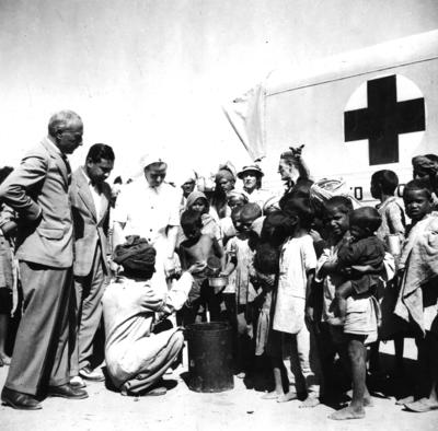 Black and white photograph. The 'milk parade' at Multan Cantonment Camp in Pakistan. Group of refugees queuing for milk.