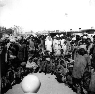 Black and white photograph. Group of refugees and Red Cross personnel, including Lady Limerick, at Multan Cantonment Camp in Pakistan