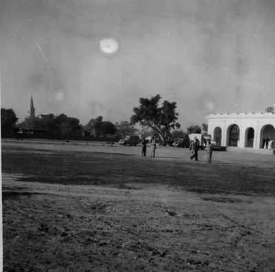 Black and white photograph. British Red Cross Society hospital wing pictured with vehicles in front, including a Red Cross ambulance, Pakistan