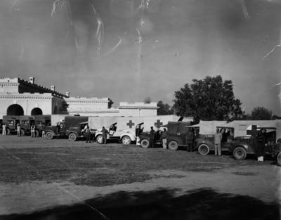 Black and white photograph. British Red Cross ambulance convoy and drivers parked outside No1 Hospital in Multan, Pakistan