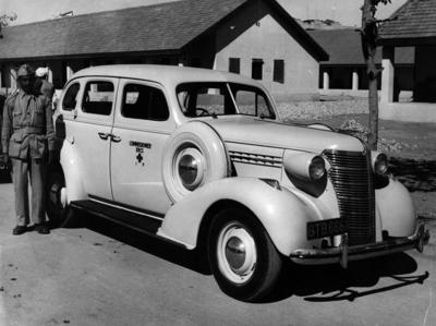 Black and white photograph. British Red Cross Commisoner's staff car with driver, Pakistan