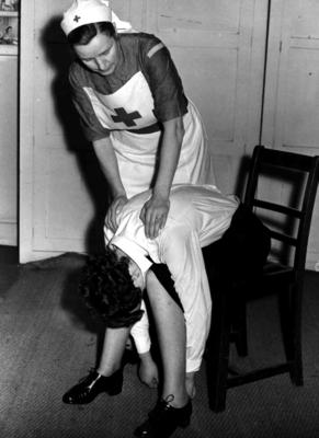 Black and white photograph. First aid training for the treatment for fainting