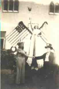 Three people in fancy dress posing with American flags