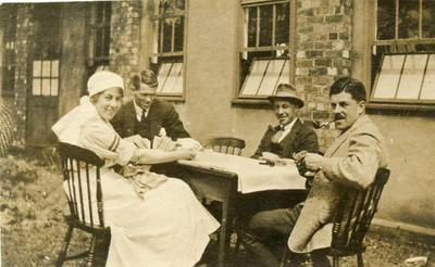 VAD member [Dorothy Hancock] in nursing uniform sitting at a table playing cards with male [patients] at [Southmead Hospital, Bristol]