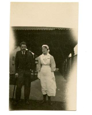 VAD member [Dorothy Hancock] in nursing uniform walking with a patient with a walking stick at [Southmead Hospital, Bristol]