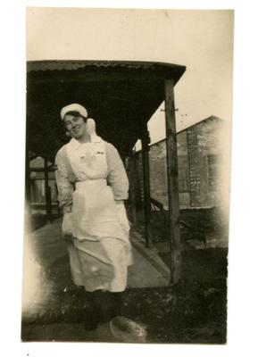 VAD member [Dorothy Hancock] in nursing uniform walking in the grounds of [Southmead Hospital, Bristol]
