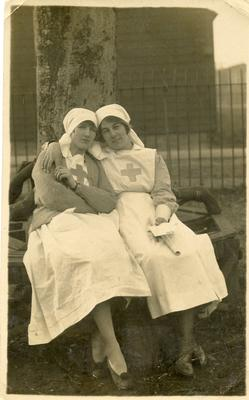 Dorothy Hancock and another VAD in nursing uniform sitting on a tree bench in the grounds of [Southmead Hospital, Bristol]