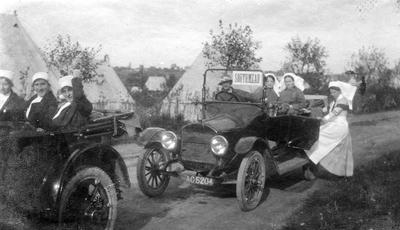 Seven Red Cross nurses in two cars driving away from a camp