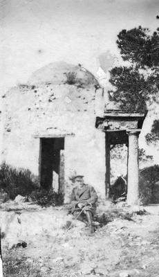 One male member in outdoor uniform with a walking stick sitting in front of an unidentified building