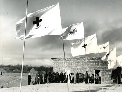 Black and white photograph. Emergency relief houses in Cheskin, Iran. Opening ceremony, view of building with crowd of people standing in front, line of flags in foreground.