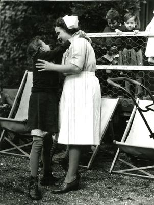 A child embracing a nurse who is helping her to stand at the Palace School in Ely