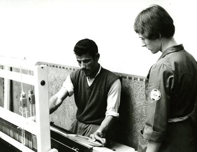 Black and white photograph. Therapy for a seriously disabled patient in Morocco, man being taught weaving by a Red Cross occupational therapist.