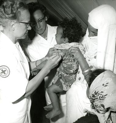 Black and white photograph. Swedish Red Cross medical team vaccinating a child at the Algerian border crossing-point at Beni Drar.