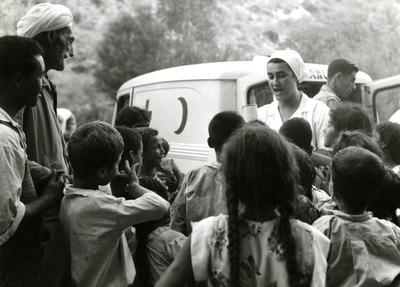 Black and white photograph. A nurse distributing relief supplies to children at Port Say.