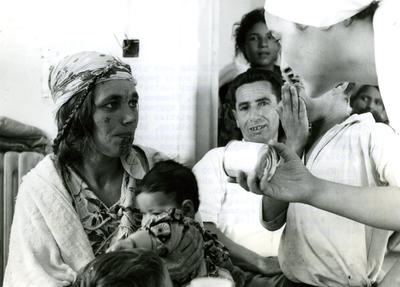 Black and white photograph. Distribution of relief supplies to refugees, woman with child being given a tin of food by Red Cross team member.