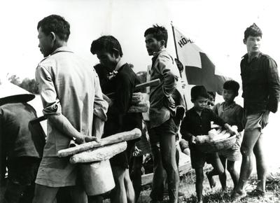 Black and white photograph. Victims of flooding in Vietnam receiving food