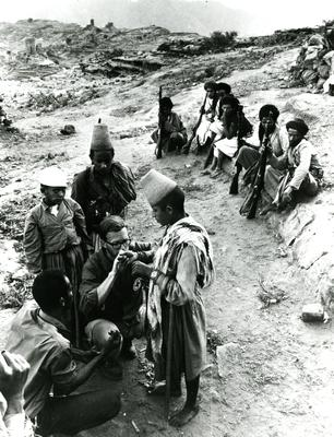 Black and white photograph. Providing medical aid in the Yemen. Red Cross doctor examining the hand of a young man, soldiers seated in background.