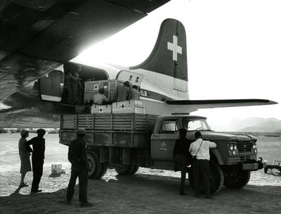 Black and white photograph. Unloading relief supplies in Najran