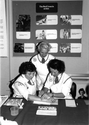 Three Red Cross volunteers practising skin camouflage treatment