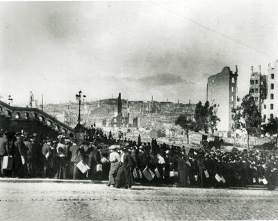 Black and white photograph of crowds lined up on the Van Ness Avenue to pick up relief supplied from the American Red Cross after the San Fransisco Earthquake 1906