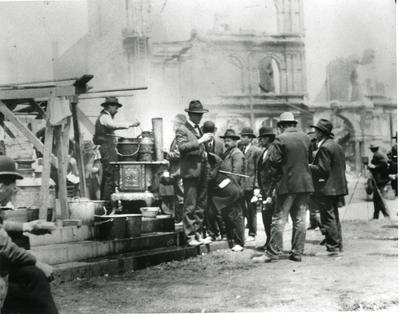 Black and white photograph of homeless men waiting for a meal after the San Fransisco Earthquake 1906
