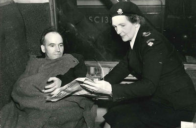 Black and white photograph of a patient who has been transferred onto a train by British Red Cross members with the aid of the special stretcher