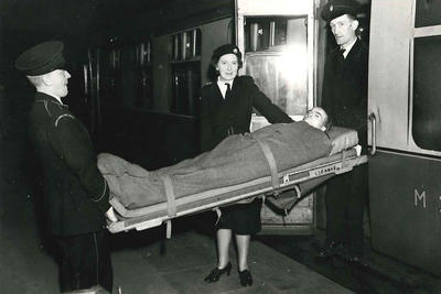 Black and white photograph of a patient on the special stretcher being transferred to a train by British Red Cross members