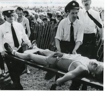 Black and white photograph of First Aid in action with help being given to an exhausted marathon runner