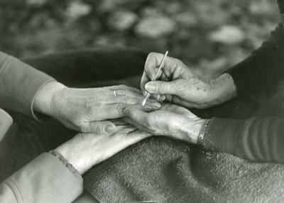 Black and white photograph of a British Red Cross service user getting a manicure