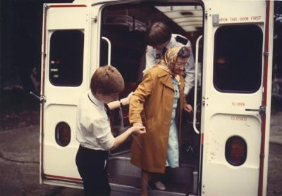 Colour photograph of Red Cross Youth members helping an elderly lady out of an ambulance