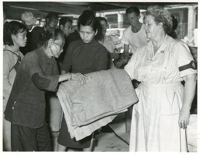 Black and white photograph of clothing distribution after a fire in Hong Kong