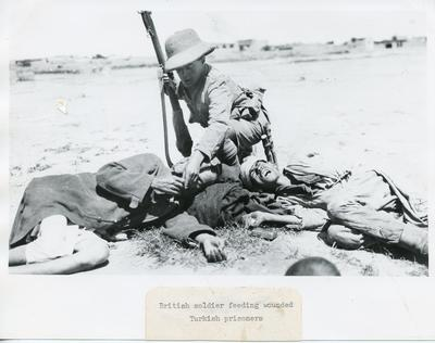 Black and white photograph of a British Soldier feeding a wounded Turkish prisioner during the First World War