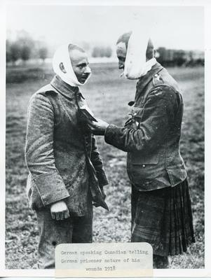 Black and white photograph of a German speaking Canadian telling the German prisoner the nature of his wounds
