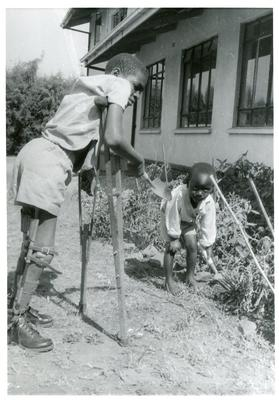 Black and white photograph of disabled children gardening near to the British Red Cross office in Malawi