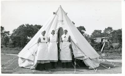 Black and white photograph of three British Red Cross members outside a bell tent