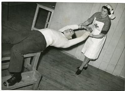 Black and white photograph of a VAD nurse going through exercises with a patient at a Royal Air Force Officers convalescent home