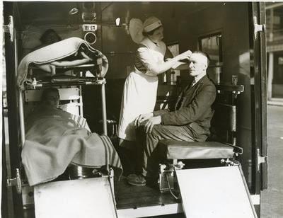 Black and white photograph of a VAD nurse at bandaging a patient in an ambulance