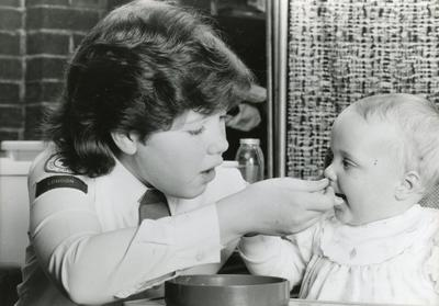 Black and white photograph of a Junior Red Cross cadet from the London branch learning infant welfare skills