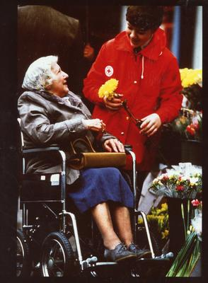 Colour photograph of a member of the Junior Red Cross giving assistance to the elderly