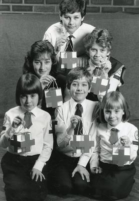 Black and white photograph of British Red Cross Youth members with the new design of collecting box