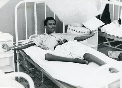 Black and white photograph of a patient undergoing rehabilitation treatment in Somalia