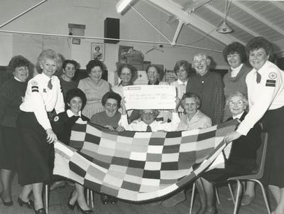 Downham Market Centre Ladies Display their Cheque at the Knit-In