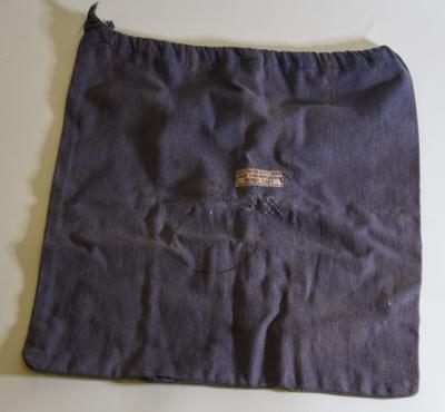 Navy blue comfort bag with sewn on label: 'Red Cross & St John War Organisation Middle East'.