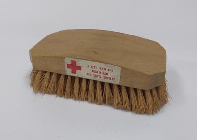 Hairbrush with sticker: 'A gift from the Australian Red Cross Society'