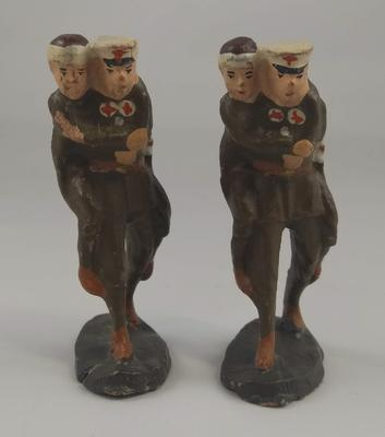 Two models each showing a wounded soldier being assisted by figure in Red Cross Uniform.