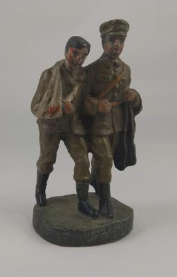 Model of soldier supporting a wounded comrade with arm in sling