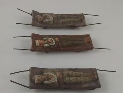 Set of three hand painted models of wounded soldiers on stretchers