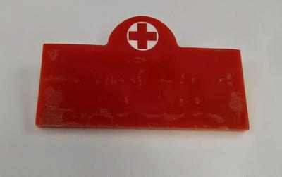 Red plastic badge with Red Cross emblem positioned in semi-circle at the top.