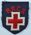 British Red Cross cloth badge: navy shield shape with embroidered emblem and letters British Red Cross