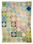 patchwork quilt of floral pattern with multi-coloured diamonds on white squares